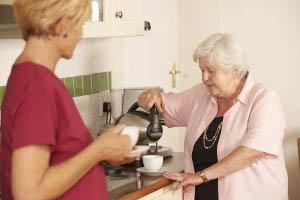 Caretaker and Senior Sharing Cup of Tea