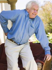 Elderly man grasping his back