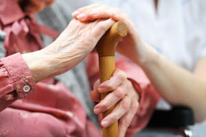 Caretaker holding elderly persons hand