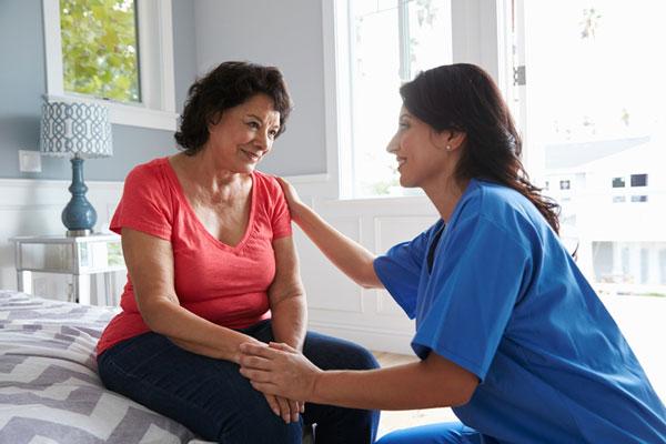 elderly women and nurse talking in home