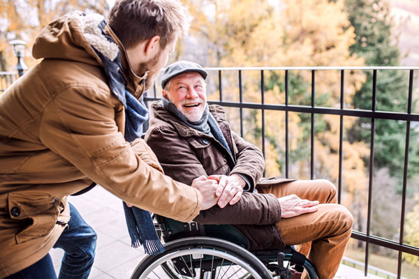 Photo of man and caregiver in fall attire looking at the beautiful leaves changing colors