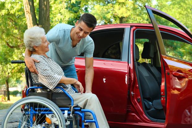 Young man helping elderly women into car