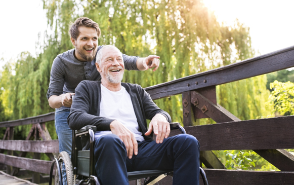 Young man pushing old man in wheelchair