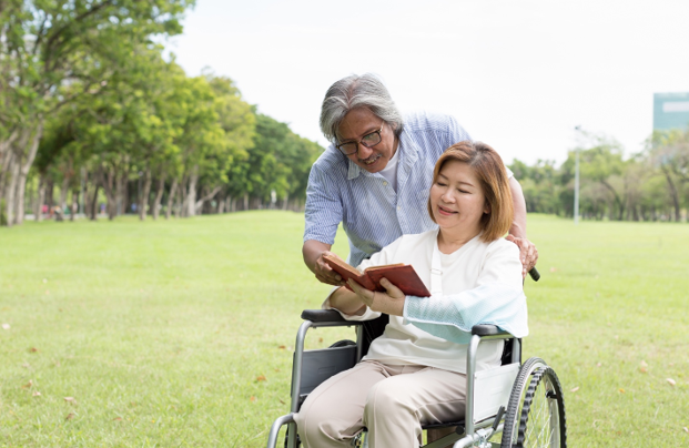 A man and women speaking and the women is holding a book in a wheelchair at a grass field