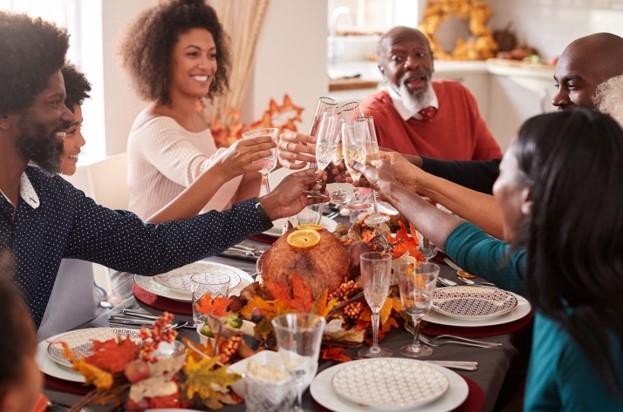 family toasting drinks over dinner