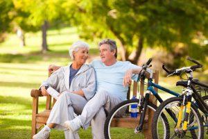 senior couple sitting on bench next to their bikes