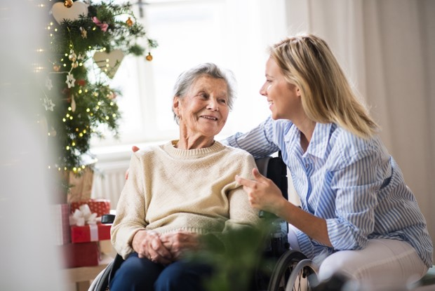 Caregiver with senior woman by Christmas tree