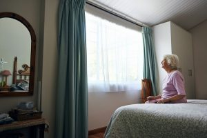 Elderly woman sitting on a bed