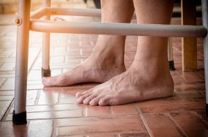 elderly persons bare feet standing with walker