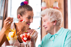 senior woman eating ice cream with younger woman