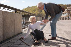 elderly woman fallen and man helping her