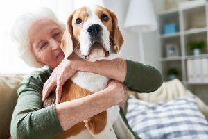 senior woman hugging dog