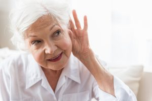 senior woman holding hand up to ear