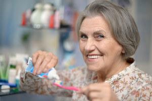 Elderly woman holding toothbrush