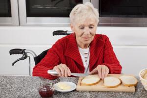 senior woman in wheelchair buttering bread