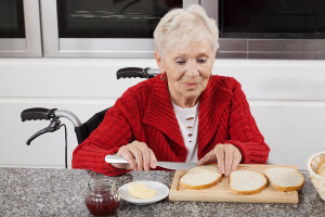 Elderly lady placing butter over a piece of bread
