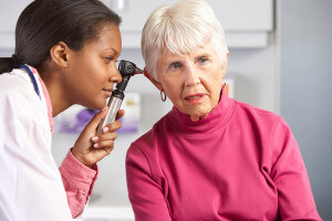 Doctor checking elderly woman's ear