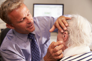 Doctor checking elderly patient's ear