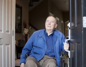 Elderly man in wheelchair opening door