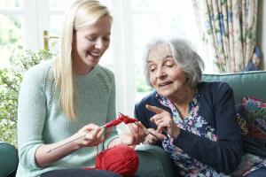 Grandmother teaching granddaughter how to crochet