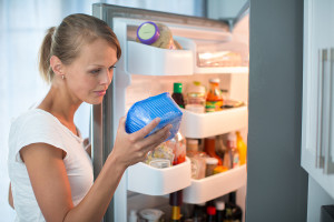 Woman checking out ice cream from refrigerator