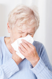 Elderly woman covering nose while sneezing
