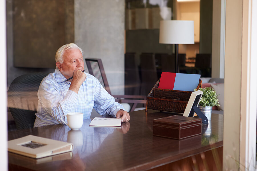 Elderly man thinking with journal and cup