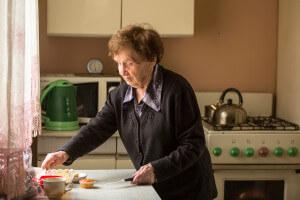 Elderly woman preparing food