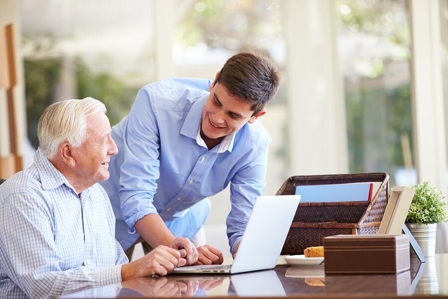 Young man teaching elderly man use laptop
