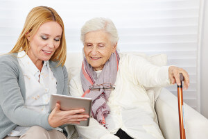 Woman guiding elderly woman to read