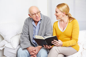 caregiver reading to elderly man
