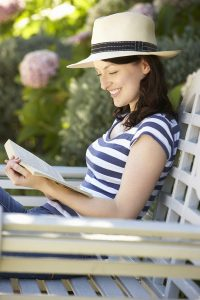 Woman in hat reading book in garden