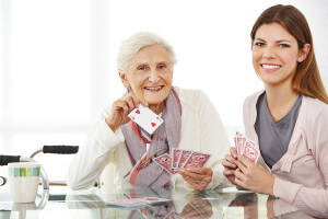 Elderly woman and caregiver playing cards