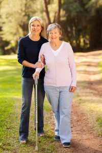 Smiling elderly woman with cane and caregiver