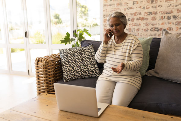 Woman on phone looking at laptop