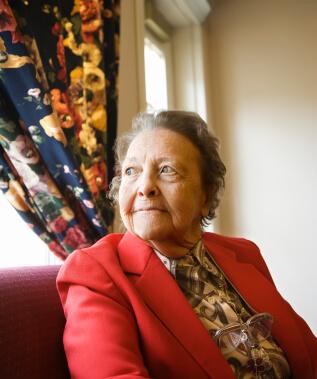 Elderly woman staring outside window