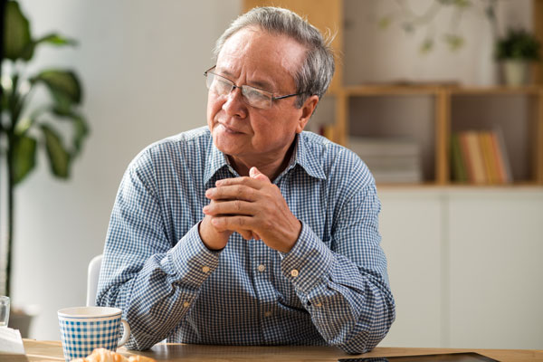 Elderly man sitting at table