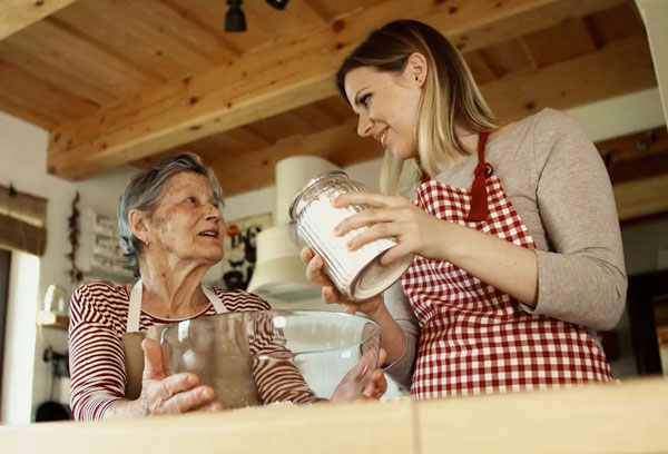 Daughter baking with elderly mother
