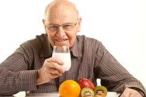 Elderly man drinking milk.