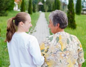 senior woman walking with caregiver in garden