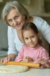 little girl making cookies with her grandmother
