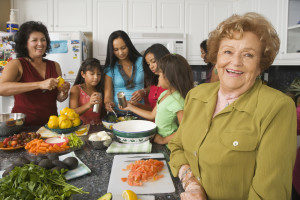 senior woman in kitchen with large family