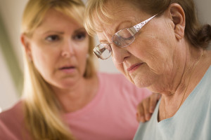 Woman consoling sad elderly mother