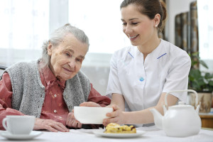 elderly woman eating with caregiver's help